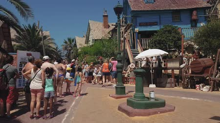 travel theme : Mellieha, Malta - August 05 2016: Popeye village theme park. Visitors reenacting scenes of Popeye 1980 musical film before wooden buildings of Sweethaven Village, turned to an attraction fun park.