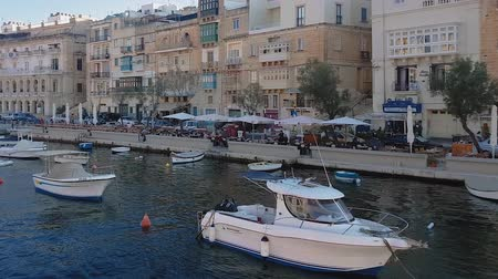 крейсерский : Three Cities, Malta Grand Harbour view from ship. Sea view of Senglea, Citta Invicta waterfront with traditional Maltese buildings and moored boats, seen from cruising ship.