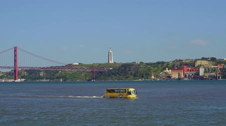 hippo : Lisbon, Portugal Hippo Trip Amphibious vehicle on Tagus river. Day view of yellow amphibious bus sailing with tourists with background view of Ponte 25 de Abril bridge & Cristo Rei statue.
