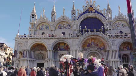 disguise : Venice, Italy Saint Mark square with crowd before Basilica during carnival. Day view of Basilica di San Marco facade with unidentified people at Piazza San Marko, during Venetian carnival celebrations Stock Footage
