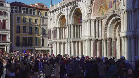 carnaval de venise : Venice, Italy Saint Mark square with crowd before Basilica during carnival. Day view of Basilica di San Marco facade with unidentified people at Piazza San Marko, during Venetian carnival celebrations Vidéos Libres De Droits