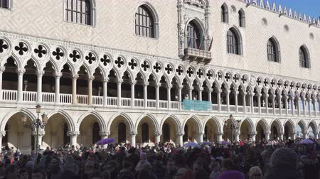disfarçar : Venice, Italy Saint Mark square with crowd before Doges Palace during carnival. Palazzo Ducale facade with people at Piazza San Marko, during Venetian carnival celebrations.