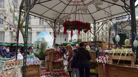 souvenirs : Vienna, Austria Easter Market Altwiener Freyung Ostermarkt. Crowd at Wien, Osterreich 2019 street market, where local vendors from Austrian regions sell decorative Easter eggs, food & drinks. Stock Footage