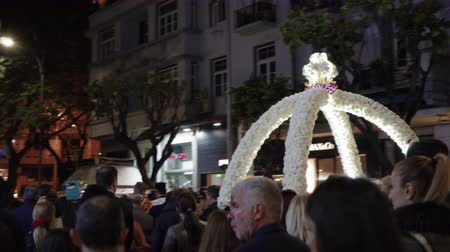 věrný : Good Friday Orthodox Easter Epitaph procession in Thessaloniki, Greece. Crowd attends the Epitaph commemoration of decorated with flowers Epitafios at night in the city center streets.