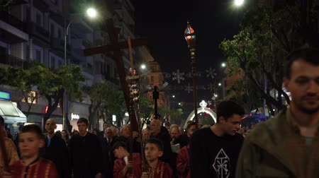 crucifix : Good Friday Orthodox Easter Epitaph procession in Thessaloniki, Greece. Crowd attends the Epitaph commemoration of decorated with flowers Epitafios at night in the city center streets.
