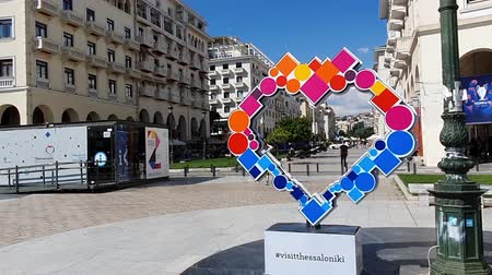 macedonian : Visit Thessaloniki, Greece sign hyper lapse at the city center. Photo opportunity frame placed at the city center, in Aristotelous main square.
