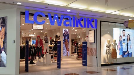 butik : LC Waikiki retailer store with illuminated logo. Turkish clothes brand trading worldwide. Store view with window showcase, inside Shopping Center Makedonia in Thessaloniki, Greece.