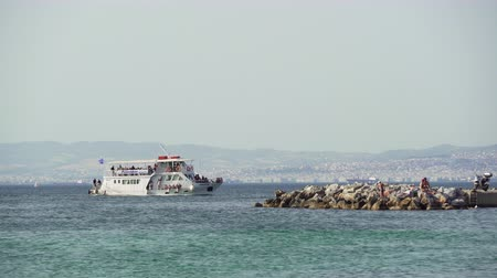 yunan : Waterbus Poseidon ship sailing Thermaic Gulf in Greece. Thessaloniki waterways small boat approaching coastal town of Neoi Epivates, with background Salonika sea view.