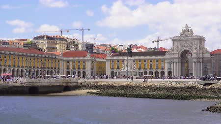 comercio : Lisbon, Portugal day sea view of Praca do Comercio with Arco da Rua Augusta. Tourists at Tagus river waterfront with passing cars before Augusta triumphal Arch & King Hose I statue at Commerce Square.