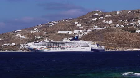 Киклады : Moored cruise ship against Greek island landscape background in Mykonos, Greece. Cycladic Island tourist ship Norwegian Spirit before whitewashed traditional Mykonean houses at Mykonos new port. Стоковые видеозаписи