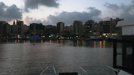 мальтийский : Valletta to Sliema ferry approaching dock in Malta. Night view of Sliema waterfront promenade with modern buildings seen from catamaran ship conducting frequent ferry service at the Maltese capital.