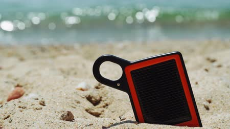 portátil : Portable solar charger power bank on the beach. Day view of small orange and black frame sun charger with black panel partly submerged on a sandy beach, with blurred sea background on a sunny day. Vídeos