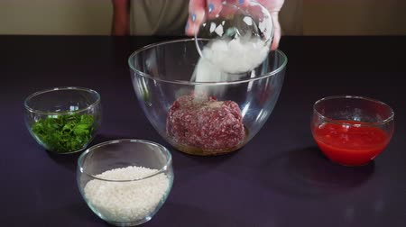 groene pepers : Stuffed peppers ingredients recipe preparation. Hand adding at transparent bowl ground chopped beef meat with olive oil and oregano, diced tomatoes, chopped white onions, uncooked rise and parsley. Stockvideo