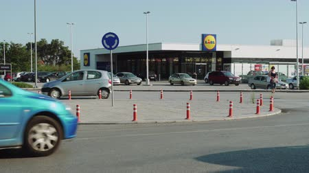 retailing : LIDL Stiftung German chain supermarket exterior with company logo and parking lot in Greece. Day view of LIDL Hellas discount store with cars on parking space at Thessaloniki, Greece. Stock Footage