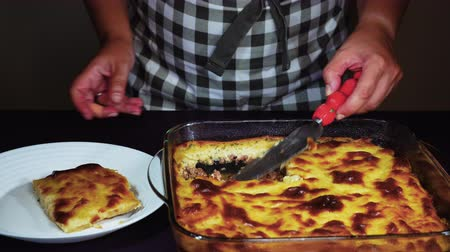 meze : Greek moussaka dish recipe preparation. Hand serving from a transparent bowl a cooked mousaka portion with bechamel white sauce, fried chopped potatoes above ground chopped beef meat. Stock Footage