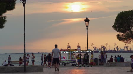 yunan : Thessaloniki, Greece Golden hour at the waterfront with crowd. Evening view of Thermaikos gulf seafront with street vendors with trailer selling cotton candy or popcorn before White Tower landmark.