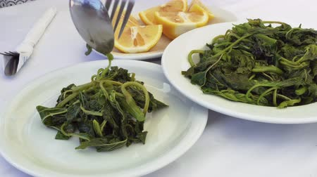 Tavern restaurant food serving with fork and spoon green blanched vegetables closeup.  Hand sprinkling fresh lemon juice on white dish with boiled leafy green salad-chorta on a tavern table in Greece.