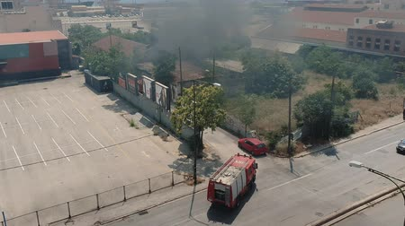 yunan : Greek Fire Service tracks approach fire next to sea port in Thessaloniki. Elevated view of Hellenic Fire Brigade vehicles closing dense black smoke rising on the sky from burning warehouse under fire. Stok Video