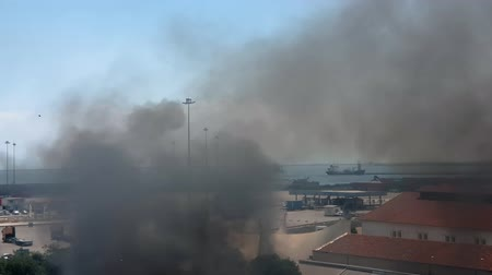 Fire next to Thessaloniki sea port in Greece. Elevated day view of dense black smoke rising on the sky from a burning warehouse under fire right next to the city commercial berthing dock pier. Dostupné videozáznamy