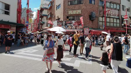 wagyu : Kobe, Japan tourists at Nankinmanhi Square on a sunny day. Day view of unidentified Asian crowd at Kobe Chinatown with Wagyu Kobe beef steak restaurants.