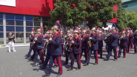 A marching band performing live. A band with musicians in characteristic uniform performs while marching during 84rth International Fair of Thessaloniki, Greece.