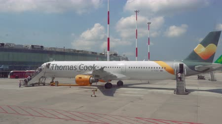 Thomas Cook Airbus A 321 taxied on Naples, Italy airport runway tarmac with boarding passengers and logo, through aircraft window. Company declared bankruptcy on 23 September 2019.