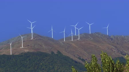 Renewable energy wind turbines arrays on vertical axis at a mountain rotating. Day view of big white wind energy converters used for electric power supply of eco friendly alternative energy. Dostupné videozáznamy