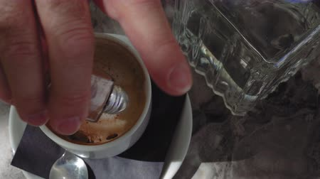 Hand sprinkling Cinnamon onto Cappuccino cup. Day sunny view of male hand adding ground cinnamon on a white cup of hot coffee on a table with a small glass dispenser sprinkler with metal lid. Dostupné videozáznamy