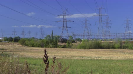 High voltage electric distribution lines on pylons at countryside. Day sunny view of arrays of overhead voltage transmission towers next to power station generating electric power in Ptolemaida Greece.