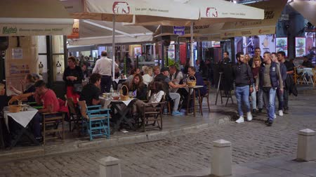 Hellenic nightlife video of people at outdoors tavern restaurants. Unidentified crowd eating & drinking at tavernas in the center at Ladadika area in Thessaloniki, Greece. Dostupné videozáznamy