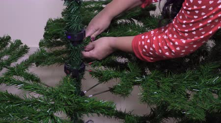 Assembling green Christmas tree inside house. Female hand adding artificial branches to shape a festive pine tree.
