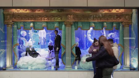 Christmas shop window showcase with passing crowd. Decorated Christmas 2019 facade of Attica department store at Tsimiski street in Thessaloniki, Greece. Dostupné videozáznamy