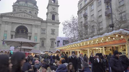 díszített : Budapest, Hungary Christmas Market by St Stephen Basilica. Day view of Advent Feast festive decorations with crowd along the traditional seasonal stalls with food and mullet wine.