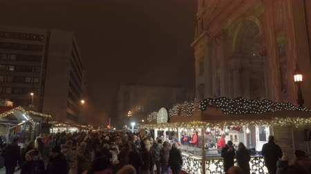 biesiada : Budapest, Hungary Christmas Market by St Stephen Basilica. Night view of Advent Feast festive decorations with crowd along the traditional seasonal stalls with food and mullet wine.