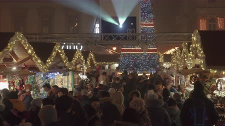 adwent : Budapest, Hungary Christmas Market & illuminated tree at St Stephen square. Night view of Advent Feast festive decorations with crowd at traditional seasonal food and wine stalls.