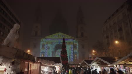 Budapest, Hungary Christmas Market at St Stephen square with decorated tree & animated show. Advent Feast laser visual projected on Basilica facade with crowd along seasonal stalls. Dostupné videozáznamy