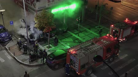 yunan : Thessaloniki, Greece Greek firefighters during fire at luxury car showroom. Elevated view of Hellenic Fire Brigade vehicles & firefighters in uniform during a night city fire.