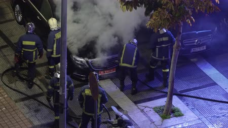 yunan : Thessaloniki, Greece Greek firefighters during fire at luxury car showroom. Elevated view of Hellenic Fire Brigade firefighters in uniform during a night city fire. Stok Video