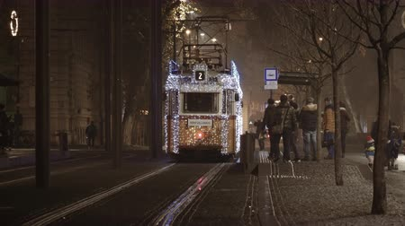 adwent : Budapest, Hungary night view of Illuminated Christmas tram on the street. Festive lights decoration of tram no.2 on track at Hungarian Parliament tram stop, Kossuth Lajos Ter M.