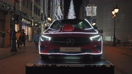 prestigious : Budapest, Hungary Christmas Market & illuminated car & tree at Fashion Street. Night view of Advent Feast festive decorations at pedestrian area with prestigious shops expanding up to Deak Ferenc UTCA Stock Footage
