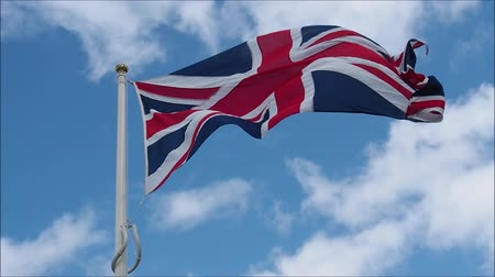 ensign : United kingdom flag or The great Britain flag waving in the wind with blue sky on sunny day.