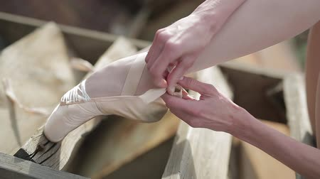 tying : Video footage close-up of a ballet dancer sitting tying ribbons on pointe