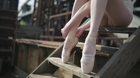 bale : Video footage close-up of a ballet dancer sitting tying ribbons on pointe