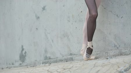 различный : Video footage of the young graceful ballerina feet close-up on a background of textured concrete wall. Legs dressed in different colored tights black and white. Стоковые видеозаписи