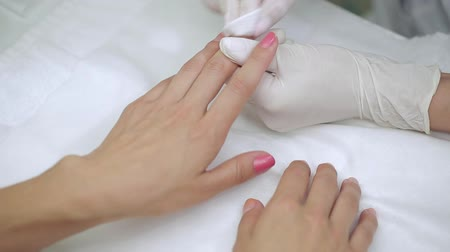 lakier do paznokci : Video footage of manicure special liquid removes old red nail polish client.