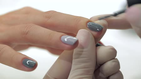 unha : Video footage of manicure at the salon. Master gets a new paint gray fingers on different - different shades. Stock Footage
