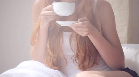 hot beverage : Woman in pajamas drinking coffee Stock Footage