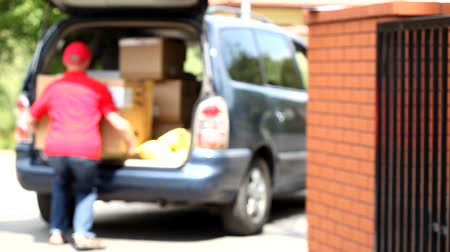 balík : Delivery man with cardboard package during work