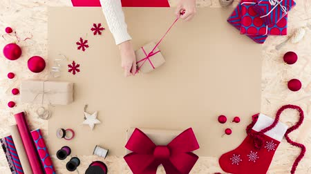 fitas : Woman tying a ribbon around Christmas present Vídeos