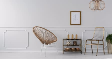 Video of a gold, elegant living room interior with a drawing on gray wall with molding, gold armchair and plants Stok Video
